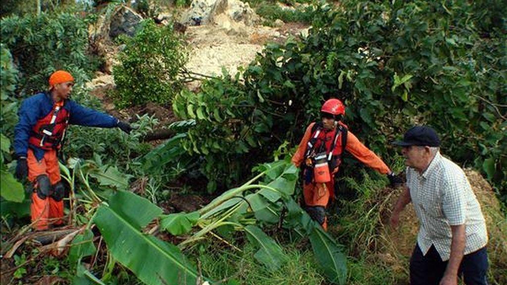 Brigadistas de la Defensa Civil ayudan a un hombre luego de un deslizamiento de tierra en la comunidad Carlos Díaz, en el municipio de Tamboril, norte de la República Dominicana, que sepultó la iglesia, un liceo y varias casas, pero que no causó muertes ni heridos. EFE