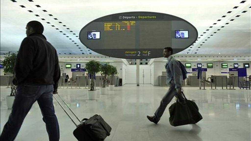 Dos pasajeros caminan en una sala de abordaje vacía en el aeropuerto Charles de Gaulle en París (Francia), tras la suspensión de todas las operaciones aéreas , debido a los fuertes vientos, que pueden alcanzar más de 100 kilómetros por hora, en la capital francesa. EFE