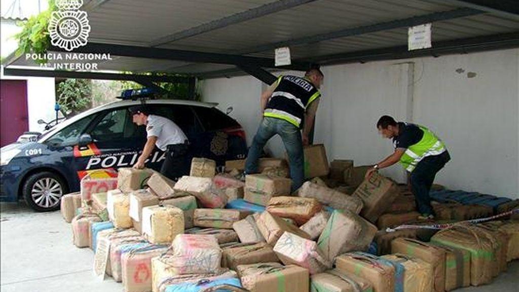 Tres policías nacionales comprueban el estado de los fardos con siete toneladas de hachís intervenidos el pasado mes de septiembre en Andalucía. EFE/Archivo