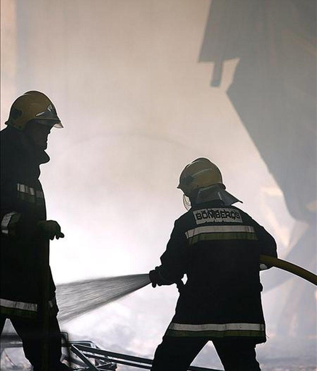 Varios bomberos trabajan en la extinción de un incendio en 2005 en el polígono Santa Cruz de la capital malagueña. EFE/Archivo