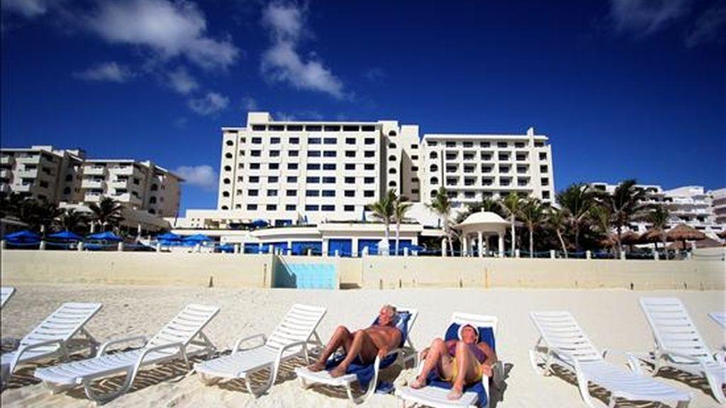 Turistas en una playa de Cancún, que acoge hasta el 10 de diciembre la conferencia de la ONU sobre Cambio Climático, y es paradigma de los efectos del calentamiento global y víctima de terribles huracanes que han dañado sus arrecifes coralinos y manglares. EFE