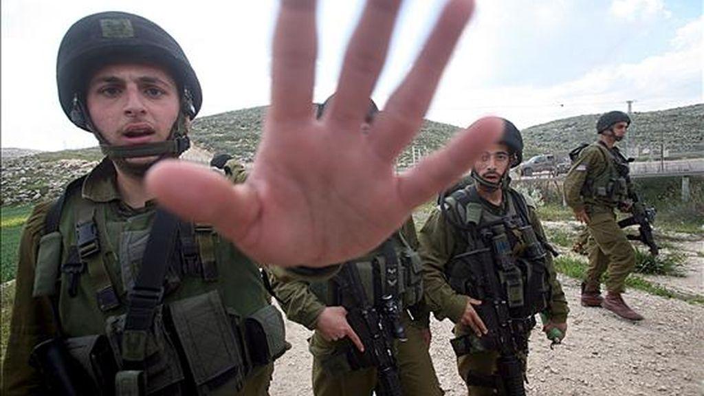 Soldados israelíes intentan impedir que se tomen fotografías de los enfrentamientos con palestinos participantes en una manifestación con motivo del Día de la Tierra en la localidad cisjordana de Idna. EFE