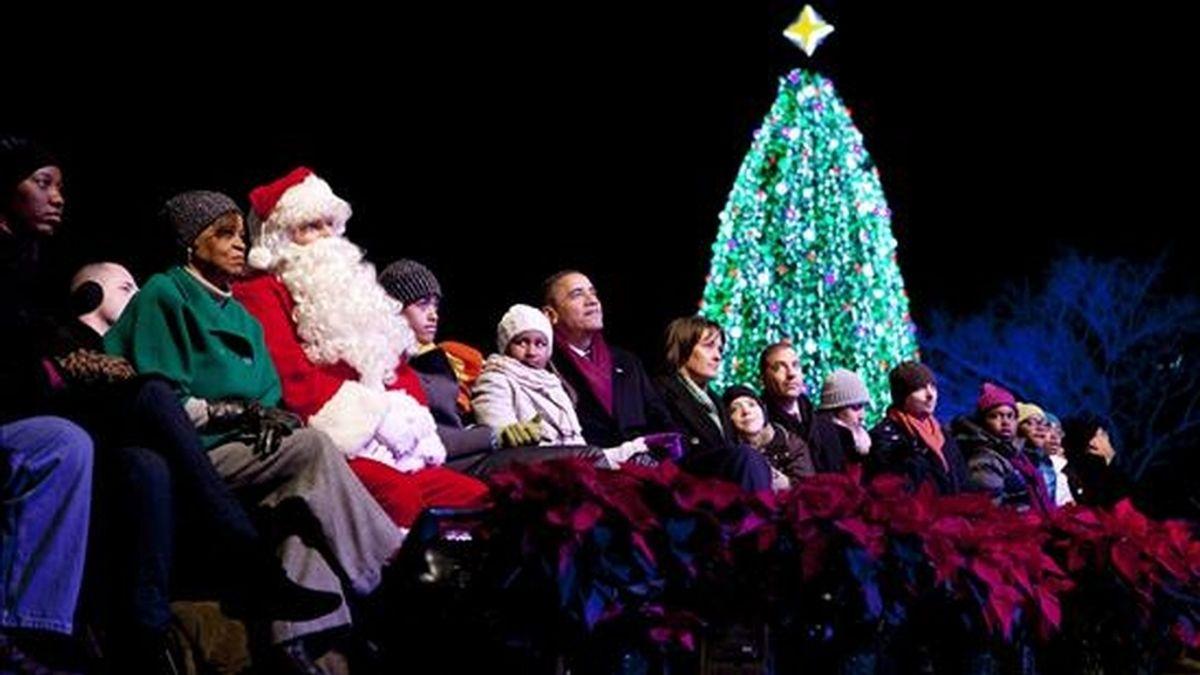 El presidente estadounidense, Barack Obama (c), la madre de la primera dama, Marian Robinson (2i), y sus hijas Malia (c) y Sasha (c) participan junto a un hombre disfrazado de Santa Claus (3i), en la ceremonia de iluminación del Árbol de Navidad Nacional cerca a la Casa Blanca, en Washington D.C. (EE.UU.). EFE