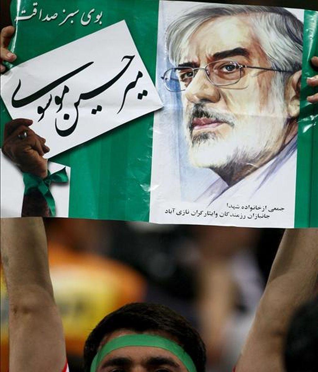 Un seguidor de la selección iraní de fútbol sostiene un cartel con la imagen del líder de la oposición, Mir Husein Musaví, durante el encuentro frente a Corea del Sur disputado hoy en Seúl. EFE