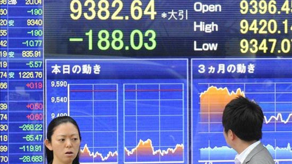 Dos personas pasan por delante de un monitor en el que se muestran las variaciones del índice Nikkei. EFE/Archivo