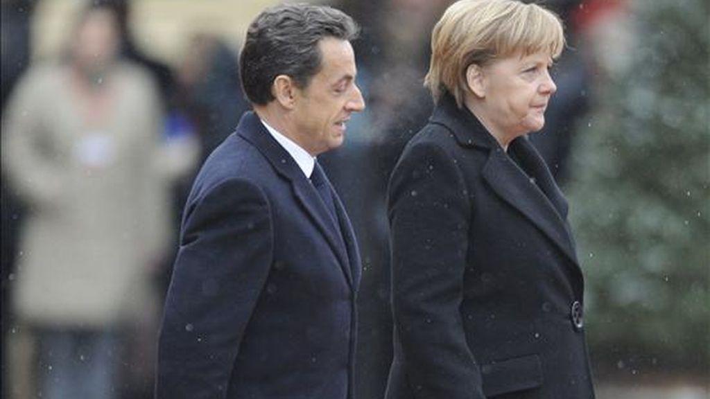 La canciller alemana, Angela Merkel (izda), y el presidente francés, Nicolas Sarkozy (dcha), inspeccionan la guardia de honor a su llegada hoy a Friburgo en Alemania. En el marco de las habituales Consultas Franco-alemanas, los dos dirigentes tratarán de estructurar una postura común en materia financiera de cara a la cumbre ordinaria de jefes de Estado y Gobierno de la Unión Europea (UE), según medios alemanes. EFE