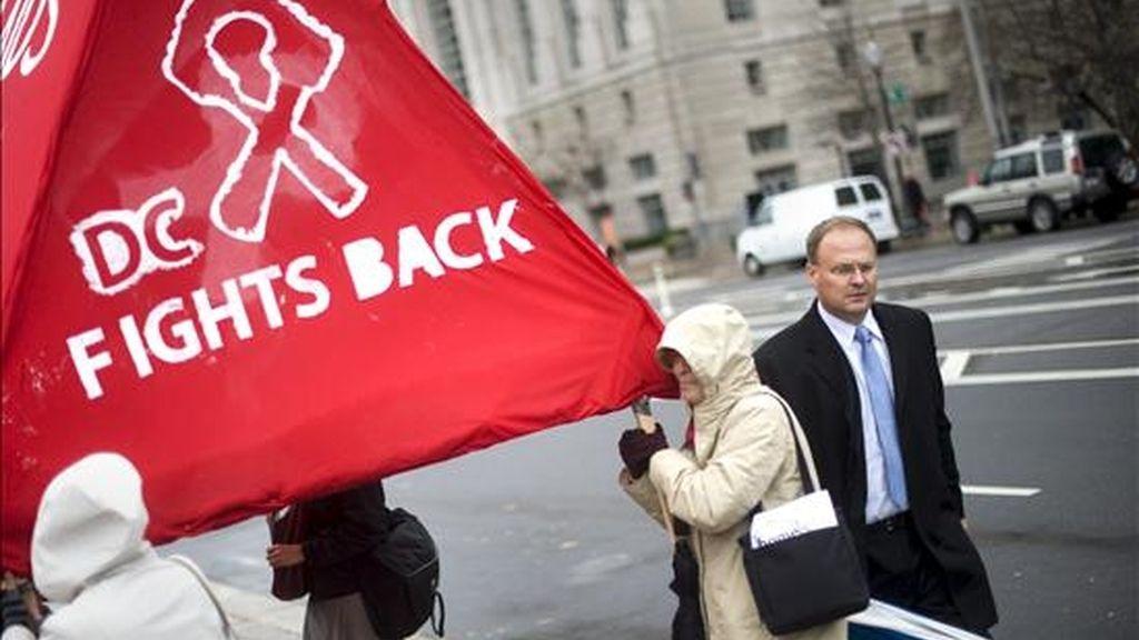 Unos activistas de la lucha contra el SIDA sostienen unas pancartas con lazos rojos en Washington, Estados Unidos. El Programa Conjunto de las Naciones Unidas sobre VIH/sida (Onusida) informó la semana pasada que en la actualidad hay 33,3 millones de personas en el mundo que viven con el virus del VIH, frente a 26,2 millones en 1999. EFE