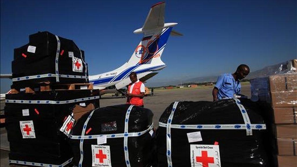 Dos hombres supervisan, en el aeropuerto de Puerto Príncipe (Haití), el material donado por la Agencia Española de Cooperación Internacional para el Desarrollo (AECID) destinado a ayudar a los enfermos de cólera. EFE