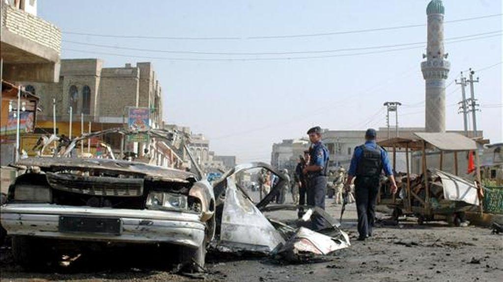Policías iraquíes inspeccionan los restos de un vehículo utilizado en un atentado con coche bomba en Bagdad, Irak ayer lunes 6 de abril de 2009. EFE/Archivo