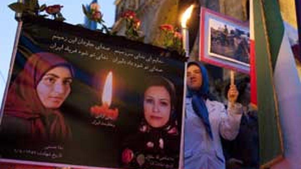 Una mujer de pie junto a las fotografías de varios víctimas iraníes durante una manifestación de apoyo a las protestas en Irán realizada en Berlín. Foto: REUTERS