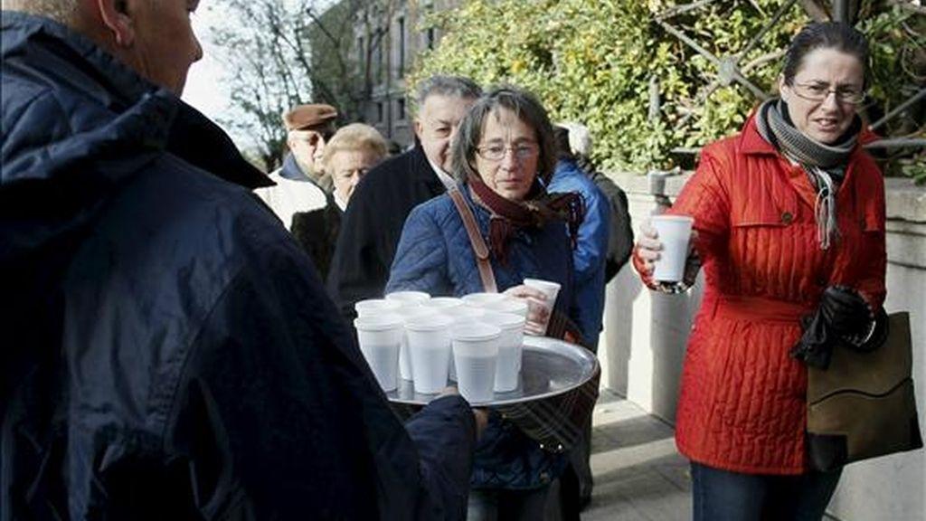 Los ciudadanos que hacen cola para visitar hoy el Senado, en el primer día de la XIII Jornada de Puertas Abiertas que concluye el próximo viernes, toman una taza de caldo para contrarrestar el frío. EFE