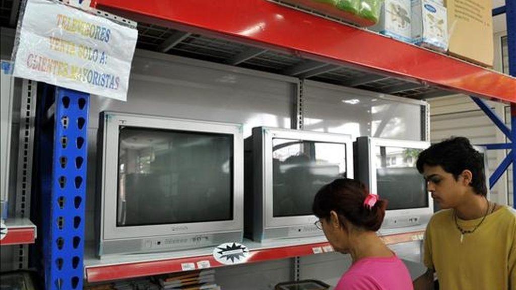 Dos personas miran estantes con televisores en una tienda. EFE/Archivo