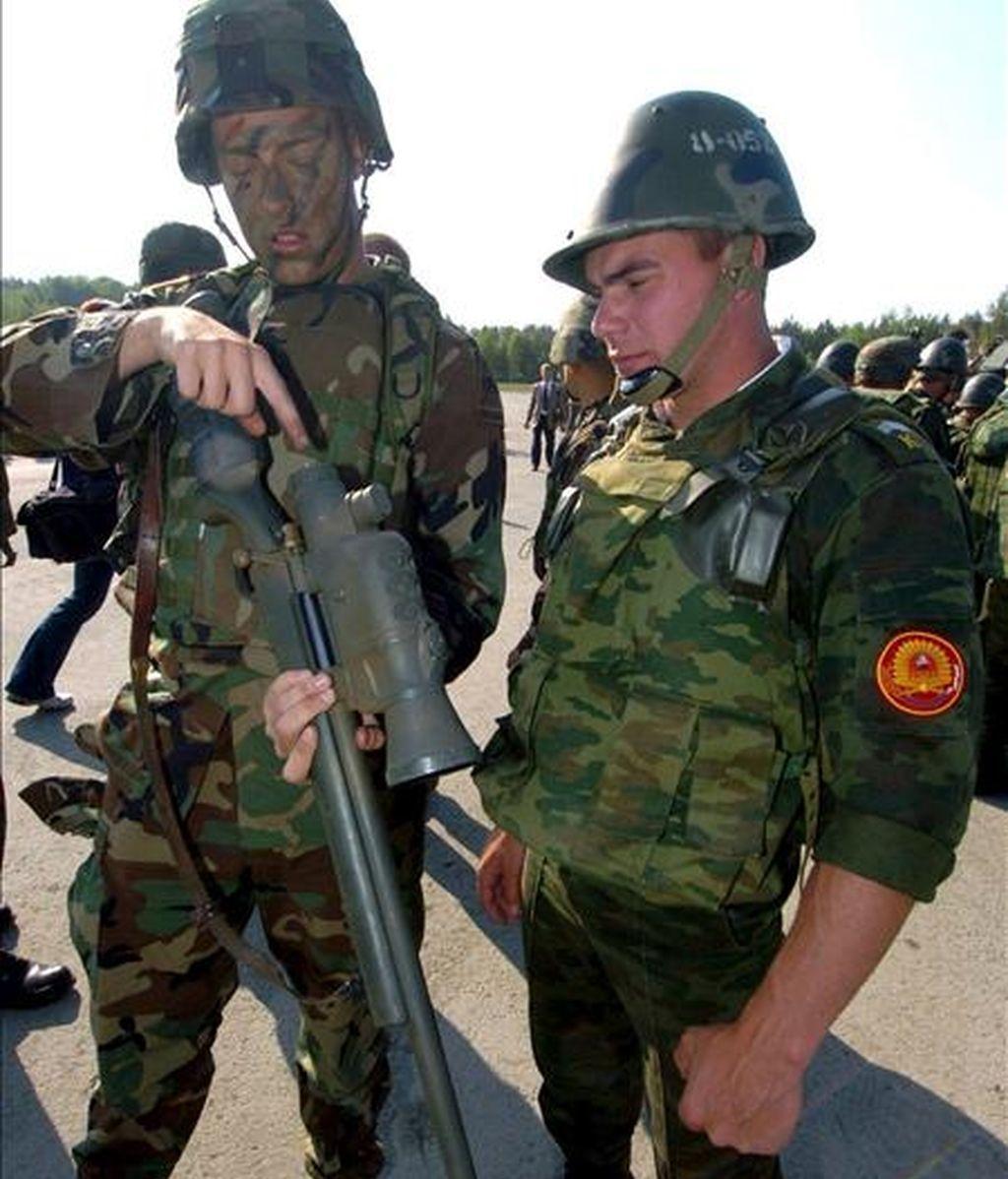 Un soldado estadounidense (izqda.) explica a un ruso (dcha.) como funciona un rifle durante las prácticas militares en Grafenwoehr, Alemania, lo 2 de junio de 2005. EFE/Archivo