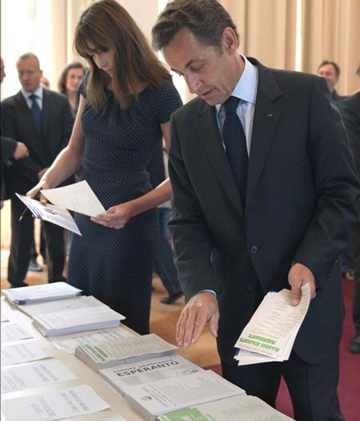 El presidente francés, Nicolas Sarkozy (d), y su esposa, Carla Bruni-Sarkozy, seleccionan unas cuantas papeletas antes de votar en un colegio electoral de París, Francia, ayer domingo,  7 de junio, durante las elecciones europeas. EFE