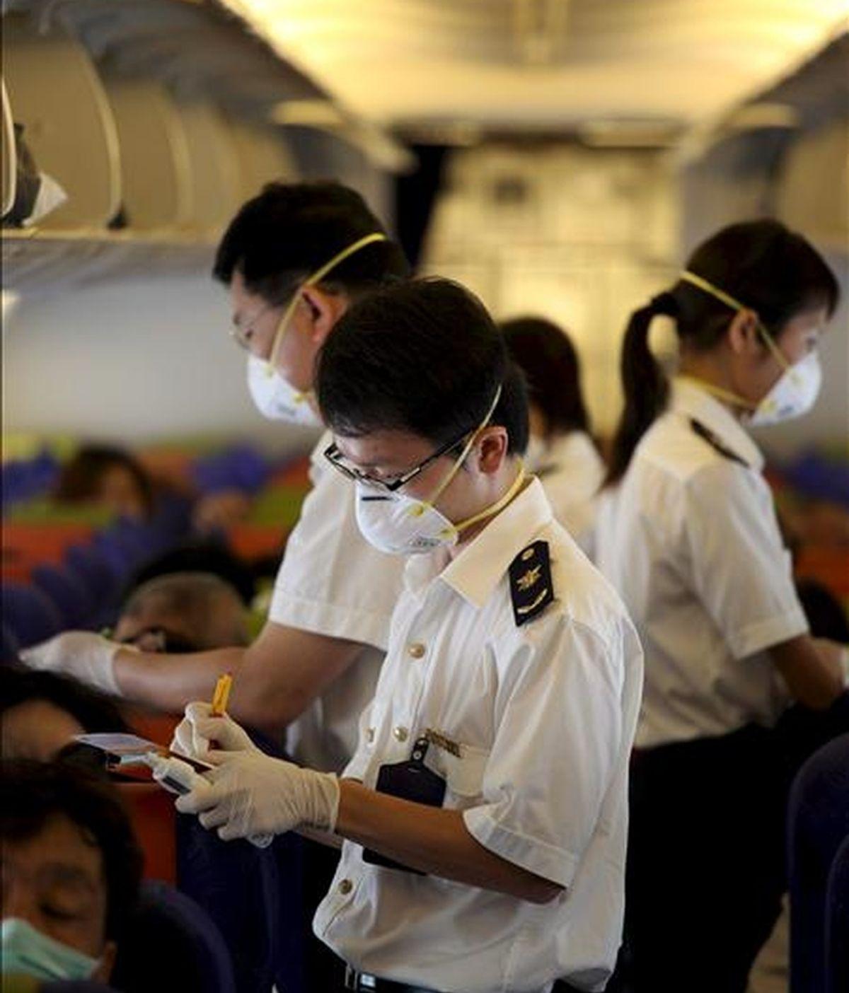 Trabajadores sanitarios inspeccionan a los viajeros en el aeropuerto chino de Meilan. EFE/Archivo