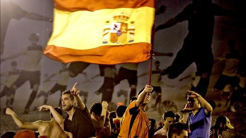Varios aficionados de la selección española celebran la victoria de su equipo en la plaza de Cibeles de Madrid tras el partido correspondiente a la final del Mundial de Sudáfrica. EFE