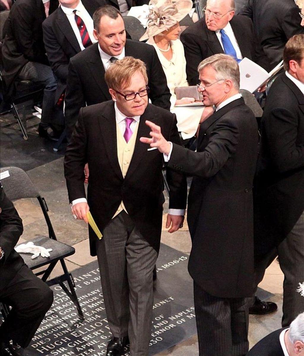 El cantante británico Sir Elton John (i) y su marido David Furnish (detrás) se disponen a tomar asiento en el interior de la abadía de Westminster para presenciar la boda entre el príncipe Guillermo y Kate Middleton, en Londres (Reino Unido), hoy, viernes, 29 de abril de 2011. EFE