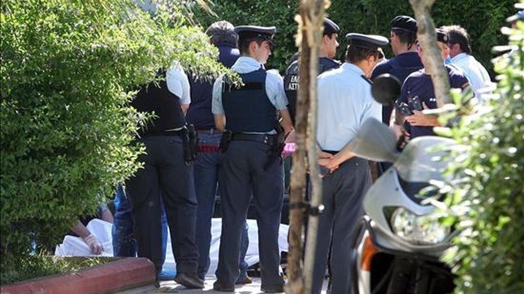 Policías de las brigadas antiterroristas griegas rodean el cuerpo del agente asesinado hoy en Atenas. EFE