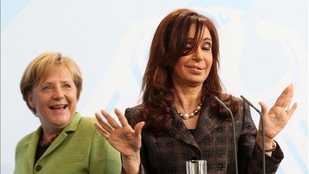 La canciller alemana, Ángela Merkel (detrás), observa a la presidenta argentina, Cristina Fernández de Kirchner, mientras ésta atiende a los medios de comunicación en la Cancillería en Berlín (Alemania) ayer miércoles, 6 de octubre. Kirchner realiza una visita oficial de tres días a este país europeo. EFE
