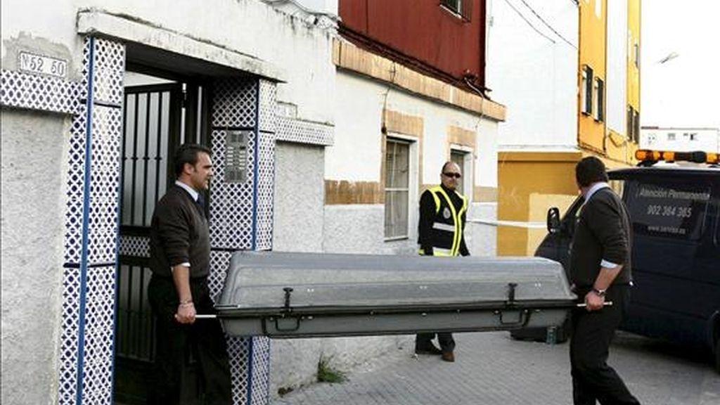 Miembros de los servicios funerarios retiran el cuerpo de una mujer de unos 30 años que ha sido hallada muerta en su vivienda en Sevilla, apuñalada presuntamente por su marido, quien a continuación se arrojó por una ventana del domicilio familiar, en un cuarto piso, y está hospitalizado en estado grave. EFE