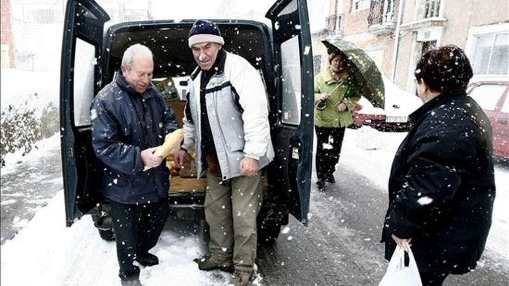 Vecinos de la localidad de Matamorosa se acercan al repartidor del pan en medio de una nevada el pasado sábado en Cantabria. EFE