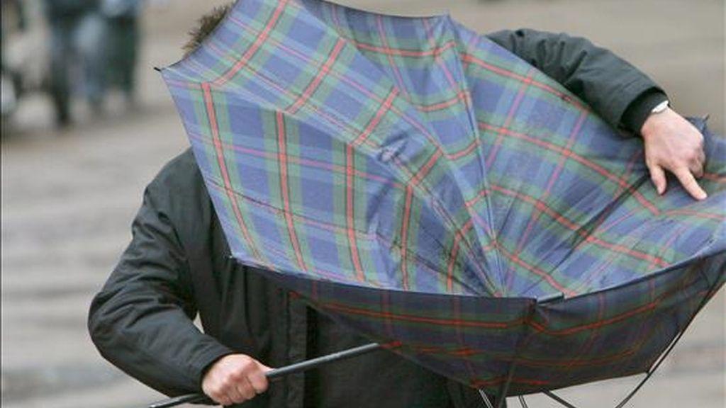 Un hombre trata de arreglar su paraguas, vuelto del revés por una ráfaga de viento. EFE/Archivo