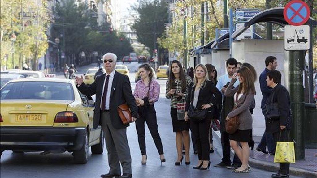 Unas personas intentan regresar a sus hogares en taxi en Atenas, Grecia, en un día de huelga. EFE/Archivo