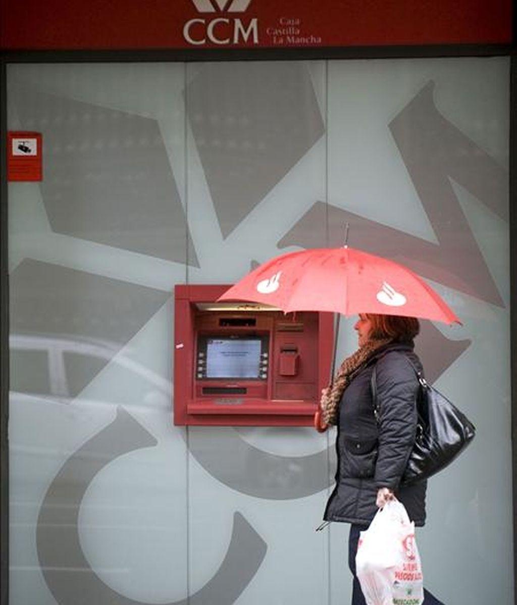Una mujer con un paraguas pasa delante de un cajero automático. EFE/Archivo