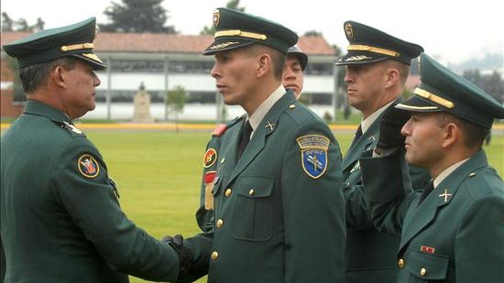 El ministro interino de Defensa y comandante de las Fuerzas Militares, el general Freddy Padilla de León (i), felicita a Juan Carlos Bermeo (2 i) durante la ceremonia de ascenso que se realizó en la escuela militar José María Córdova. EFE