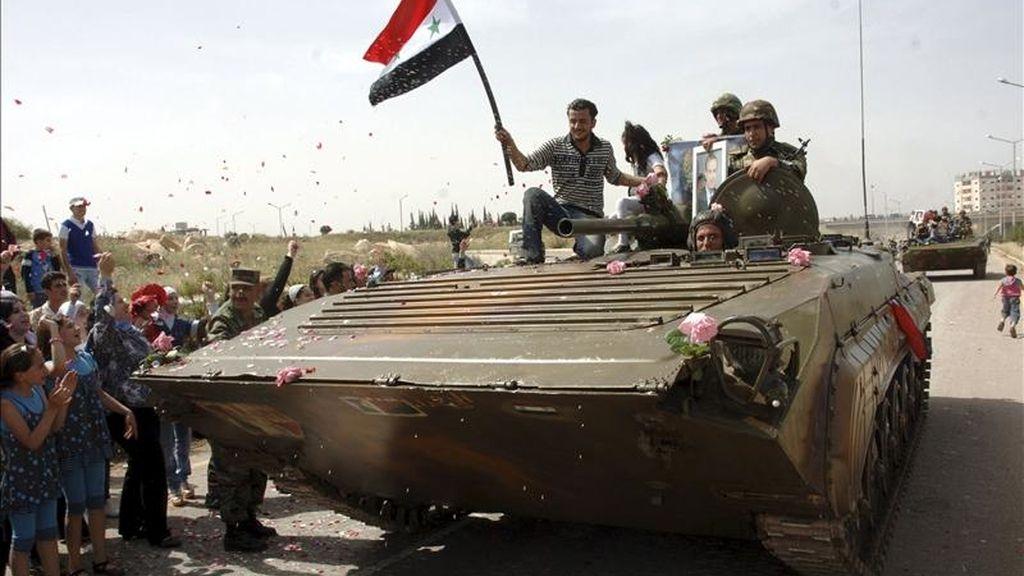 Fotografía facilitada hoy por la agencia oficial de noticias siria SANA que muestra a un residente de la localidad siria de Deraa subido en un tanque mientras el Ejército sirio se dispone a retirar sus unidades de manera gradual de Deraa ayer. EFE