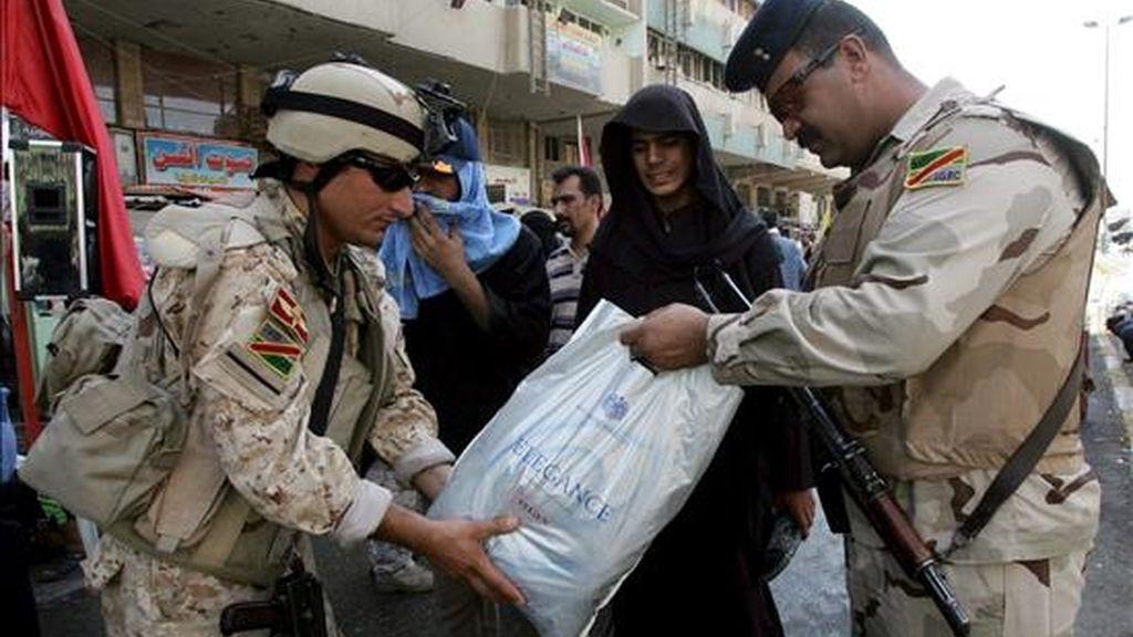 Un par de soldados iraquíes revisa la bolsa de una creyente chií que se dirige a la tumba del imán Musa Jafar al Kadim en el distrito de Kadimiya, en Bagdad (Irak) ayer miércoles, 7 de julio. EFE
