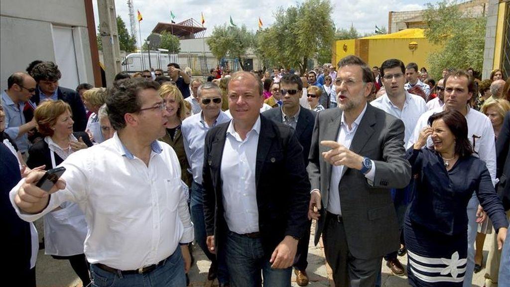 Foto facilitada por el Partido Popular (PP) de su presidente, Mariano Rajoy (d), acompañado por el candidato del partido a la Presidencia de la Junta de Extremadura, José Antonio Monago (2d), en una visita a la Feria del Jamón de Jerez de los Caballeros (Badajoz). EFE