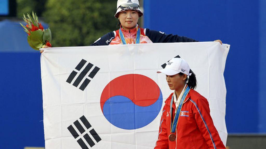 La deportista surcoreana alza la bandera al paso de la de Corea del Norte. FOTO: AP.
