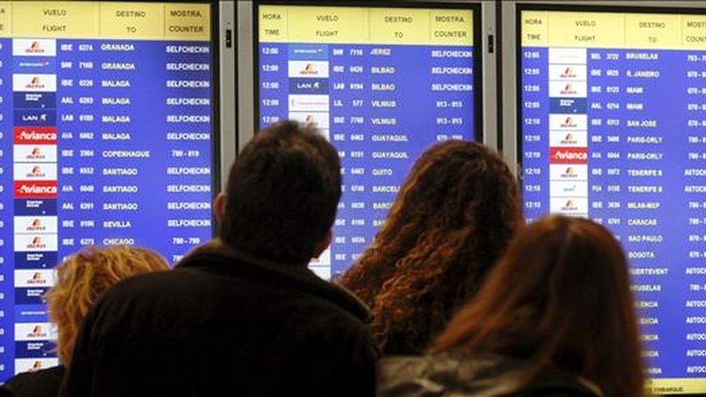 Varias personas consultan en un panel informativo el estado de sus vuelos, en el T-4 del aeropuerto de Barajas, en Madrid. EFE/Archivo