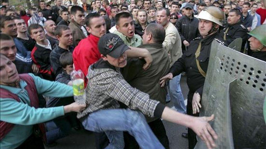 """Un grupo de manifestantes se enfrentan a la policía antidisturbios durante una protesta en las cercanías del edificio de gobierno de Chisinau, en Moldavia, hoy 08 de abril de 2009. La policía tomó bajo control el edificio del Parlamento moldavo que fue ocupado ayer durante los violentos enfrentamientos entre Policía y manifestantes, que denuncian un fraude en los comicios parlamentarios del domingo, ganados por los comunistas. Las autoridades moldavas declararon hoy """"persona non grata"""" al embajador rumano en Chisinau y acusaron a Rumanía de ser responsable de las protestas callejeras contra la supuesta manipulación de las elecciones parlamentarias. EFE"""