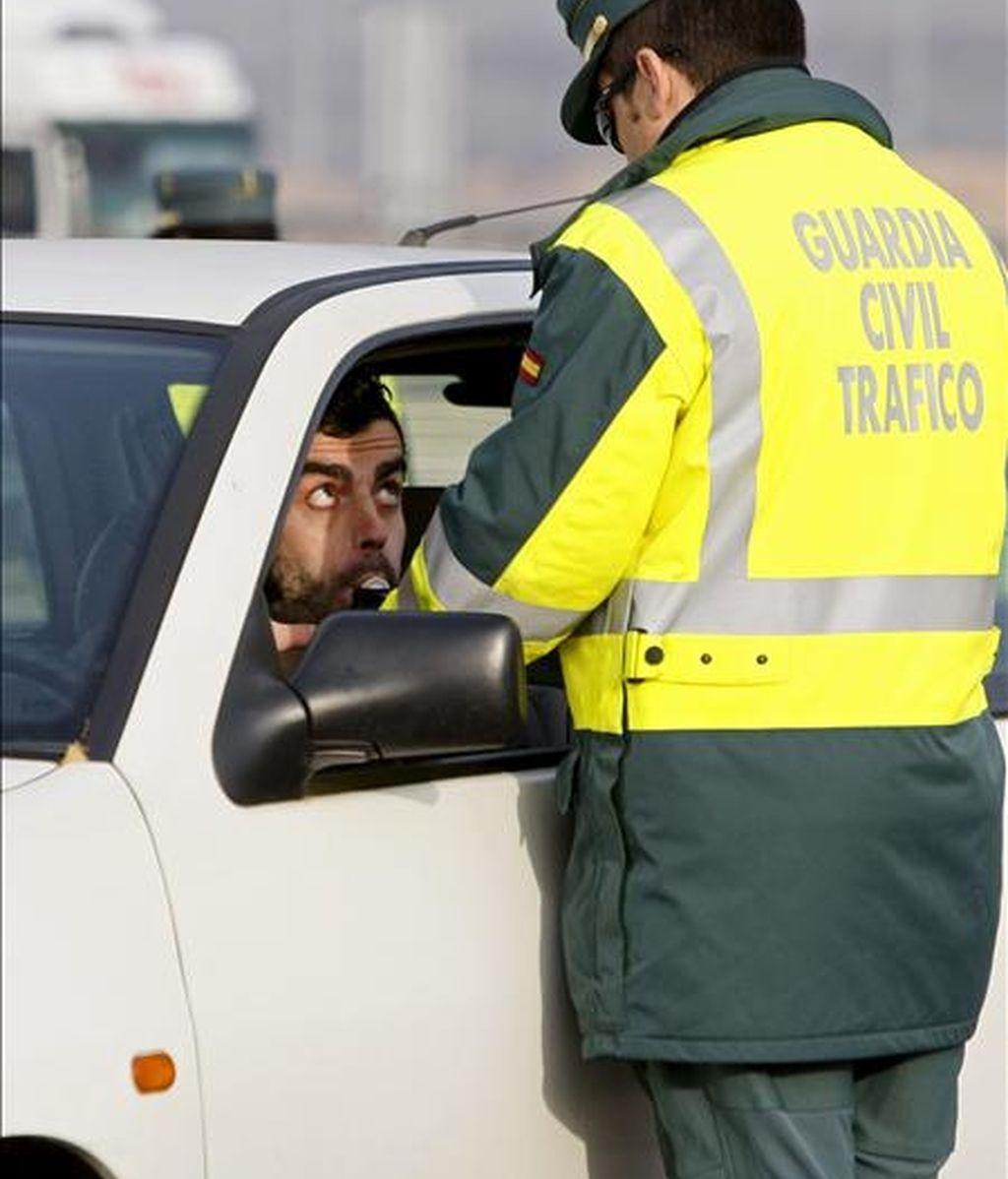 Un conductor realiza una prueba de alcoholemia a instancias de un guardia civil de tráfico en un control situado en el kilómetro 14 de la Nacional III, dentro de la campaña de Navidad puesta hoy en marcha por la DGT. EFE