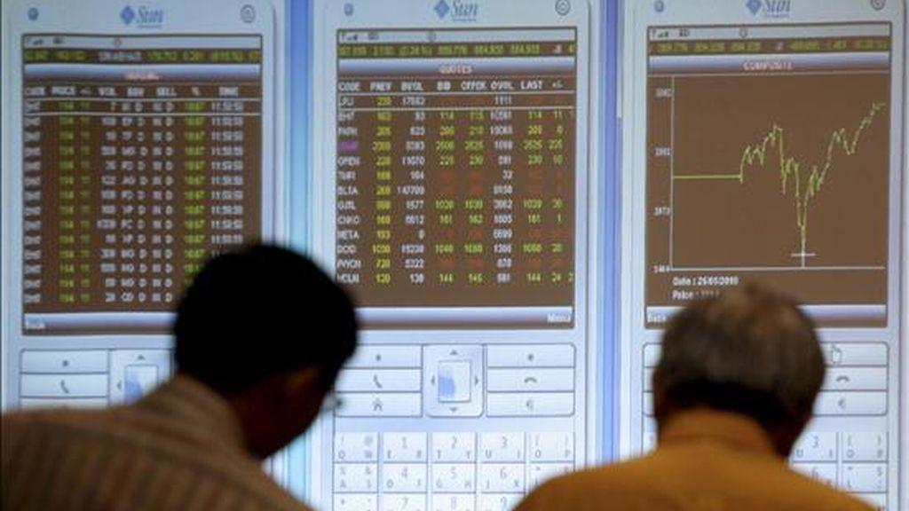 Dos inversores indonesios observan un tablero electrónico con los índices de la Bolsa de Yakarta, Indonesia. EFE/Archivo