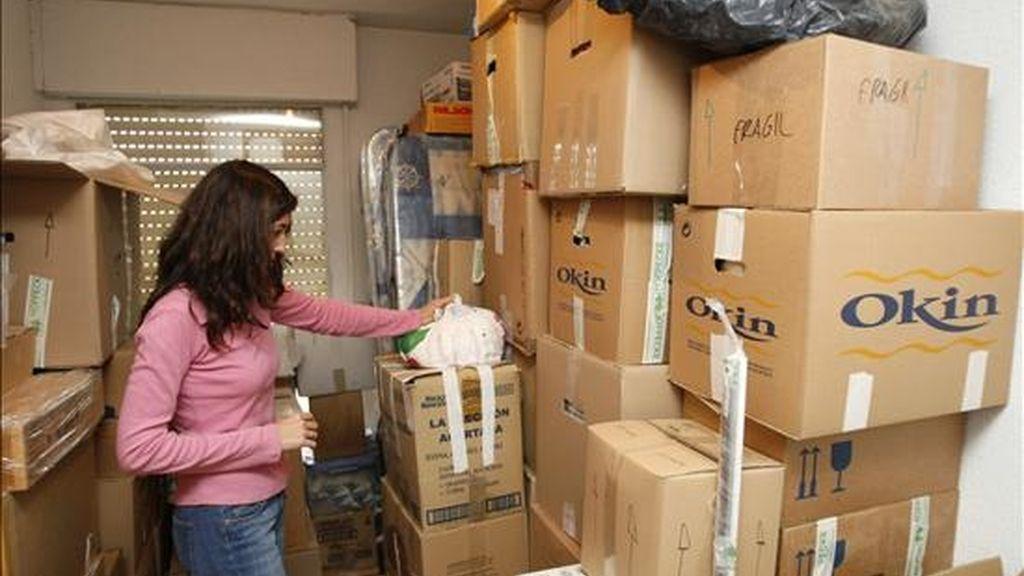 Una joven hace inventario de todas sus pertenencias, embaladas ya en cajas de cartón, momentos antes de comenzar la mudanza desde su casa. EFE/Archivo