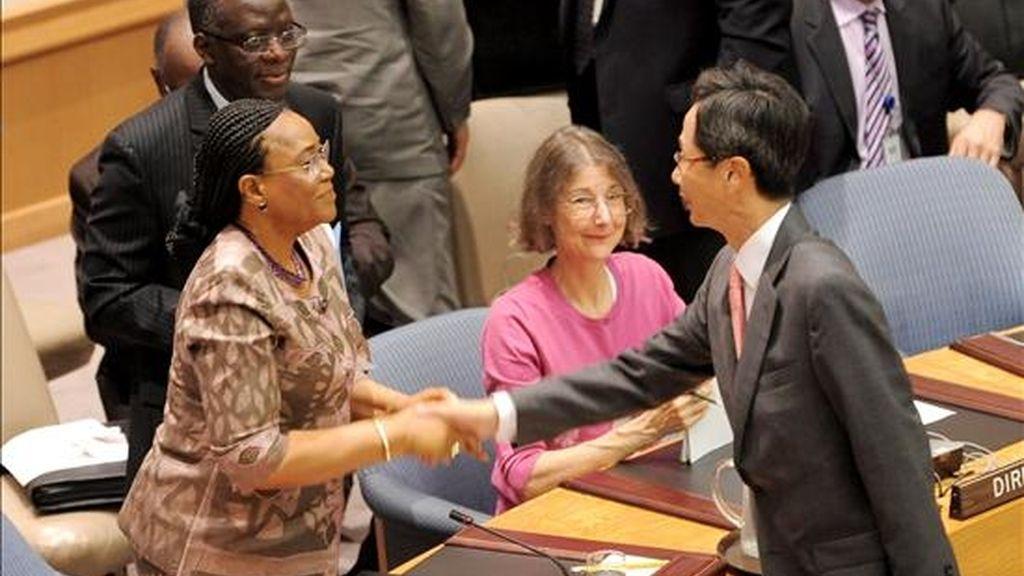 La representante permanente de Nigeria en las Naciones Unidas, Joy Ogwu (izq), estrecha la mano del embajador surcoreano en la ONU Park In-Kook tras emitir un comunicado en el que esta organización condena unánimemente el ataque contra un barco de Corea del Sur. EFE