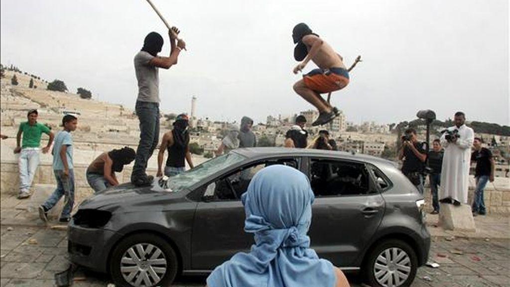 Un grupo de palestinos destrozando un vehículo israelí cerca de las antiguas murallas, en el barrio árabe de Siluán, en Jerusalén Oriental, este miércoles. EFE