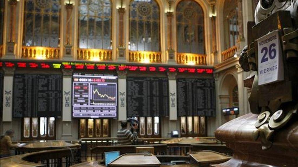 Varios operadores, durante la sesión de hoy de la Bolsa de Madrid, cuyo principal indicador, el ÍBEX 35, duplicaba a mediodía las pérdidas de la apertura, con una caída del 2,20 por ciento. EFE