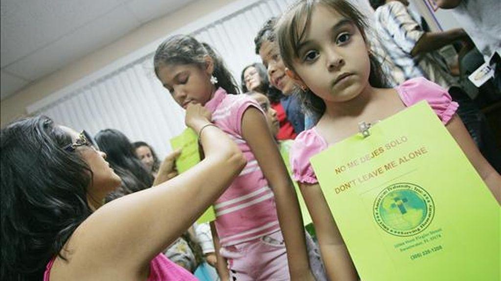 """Una niña hija de padres nicaragüenses muestra un cartel que dice """"no me dejes solo"""", en la Fraternidad Americana de Miami (EEUU), durante la manifestación de un grupo de niños cuyos progenitores han sido deportados. EFE/Archivo"""