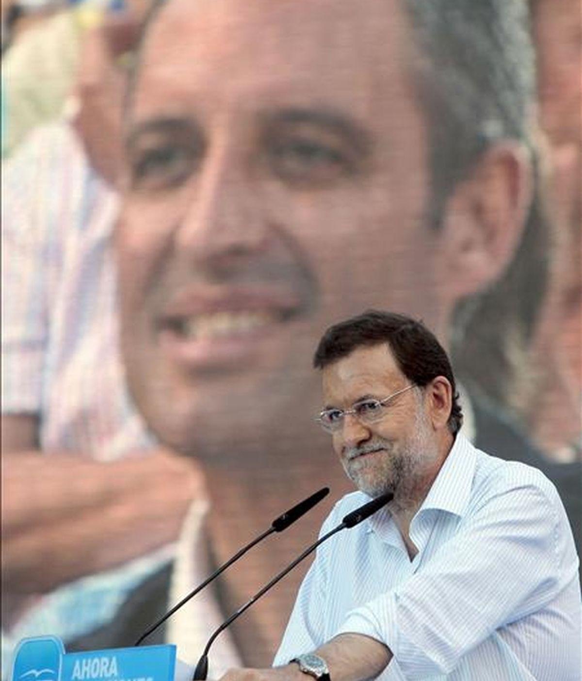El presidente del PP, Mariano Rajoy, interviene, con la imagen de Francisco Camps de fondo, en el mitin celebrado hoy en la Plaza de Toros de Valencia. EFE