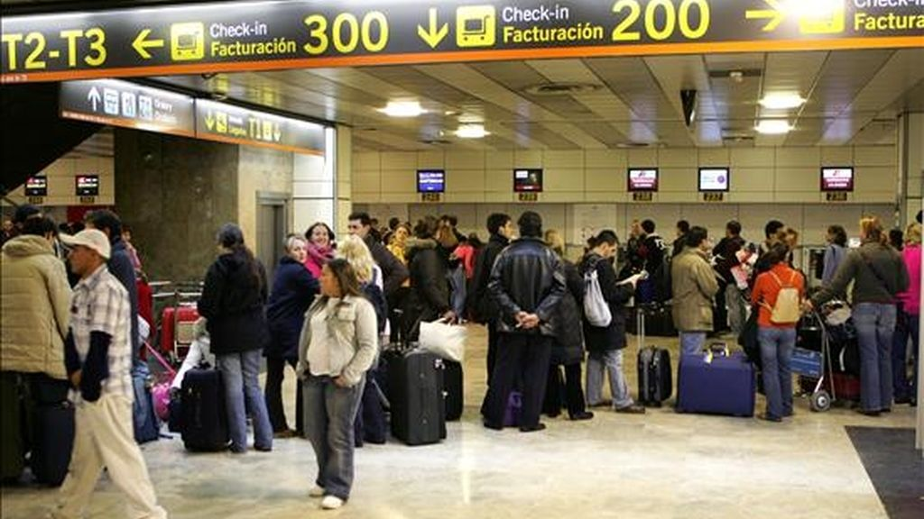 Decenas de personas hacen cola para facturar sus maletasen el madrileño aeropuerto de Barajas. EFE/Archivo