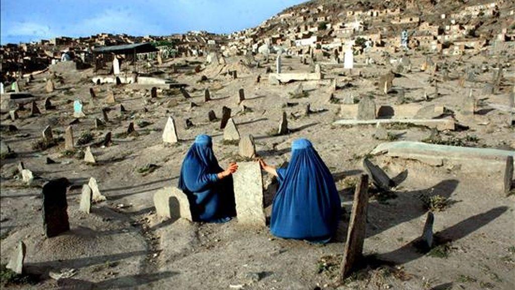 """Dos mujeres afganas vestidas con burkas visitan las tumbas de algunos de sus familiares, en un cementerior de Kabul, Afganistán. El secretario de Defensa estadounidense, Robert Gates, advirtió hoy de que se espera una estación estival de """"fuertes enfrentamientos"""" en Afganistán, por la presión que supondrá para la insurgencia la llegada de nuevas tropas de la Fuerza Internacional de Asistencia a la Seguridad (ISAF). EFE"""