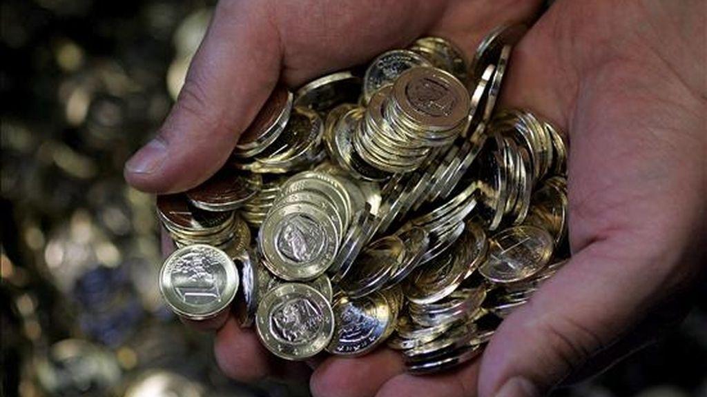Un empleado de la Casa de la Moneda sostiene monedas de un euro. EFE/Archivo