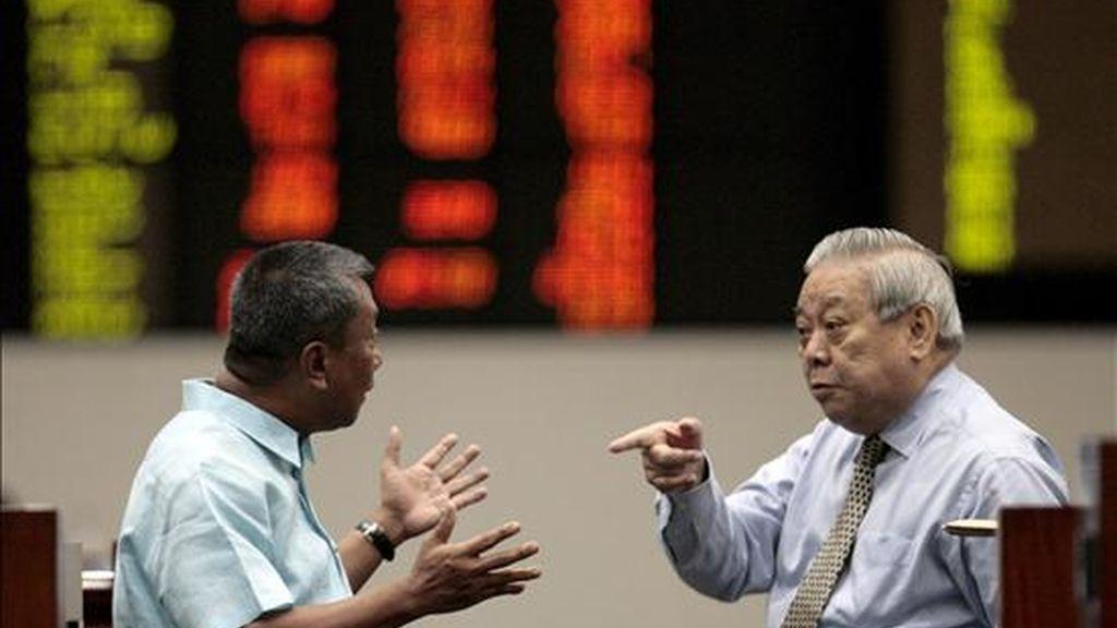 Dos corredores de bolsa filipinos conversan frente a un tablero electrónico con los índices de la Bolsa de Valores de Manila en el distrito financiero de Makati. EFE/Archivo
