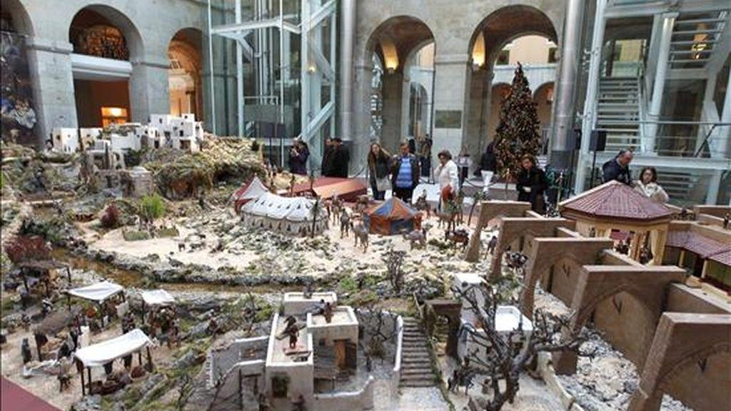 Varias personas observan el tradicional Nacimiento de 700 figuras que la Asociación de Belenistas de Madrid instala en la Real Casa de Correos. EFE/Archivo