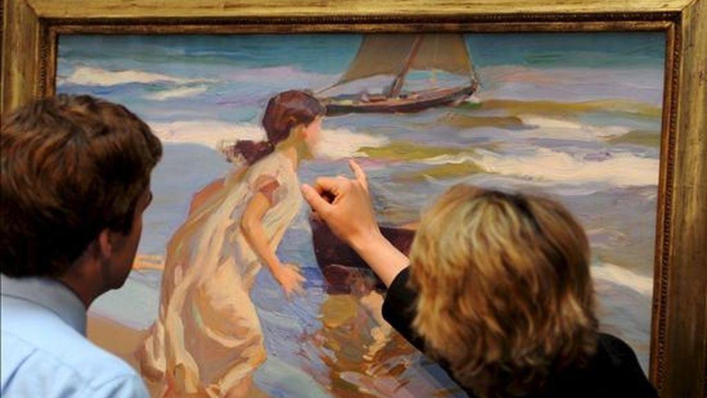 """Unas personas observan el cuadro """"Niña entrando en el baño"""", del pintor español Joaquín Sorolla, fechado en 1917 aunque acabado dos años antes, en la sede de Sotheby's en Londres (Reino Unido), el 29 de mayo pasado. EFE/Archivo"""