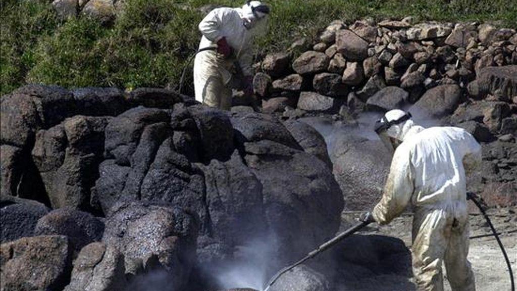 Operarios municipales limpian con agua a presión fuel de las rocas en la playa de O Pindo, en Carnota. EFE/Archivo